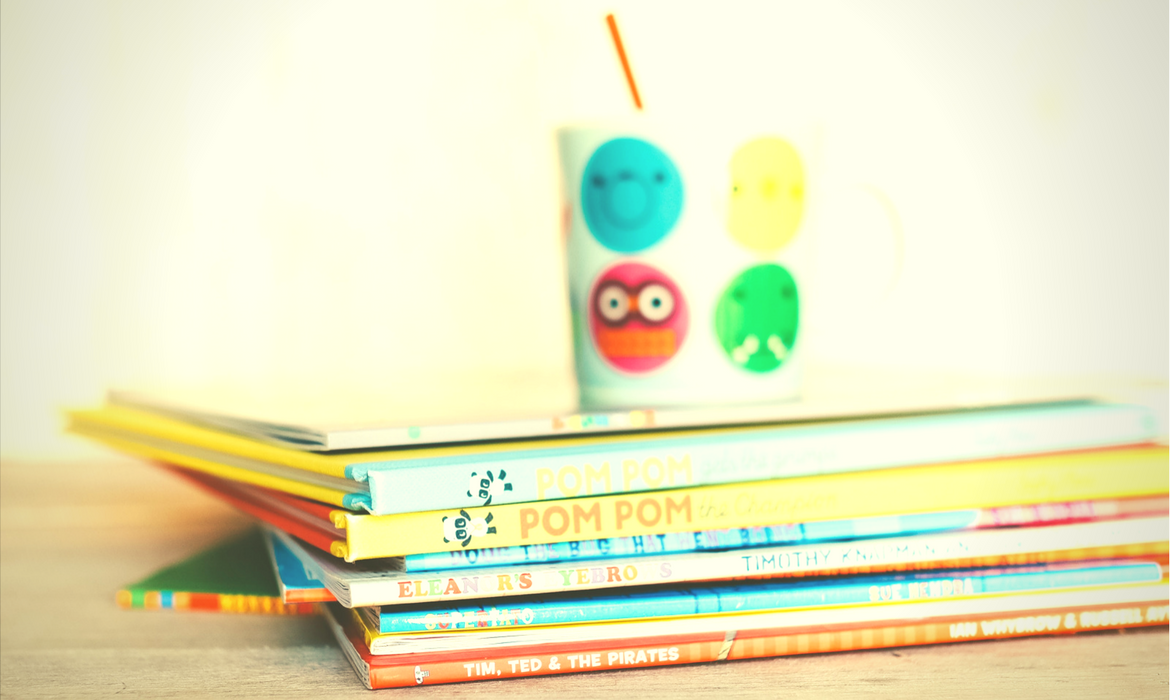 Children's books in a stack with a cup