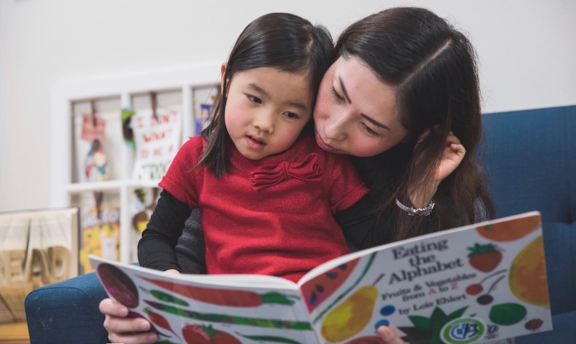 Mother and daughter reading a picture book together