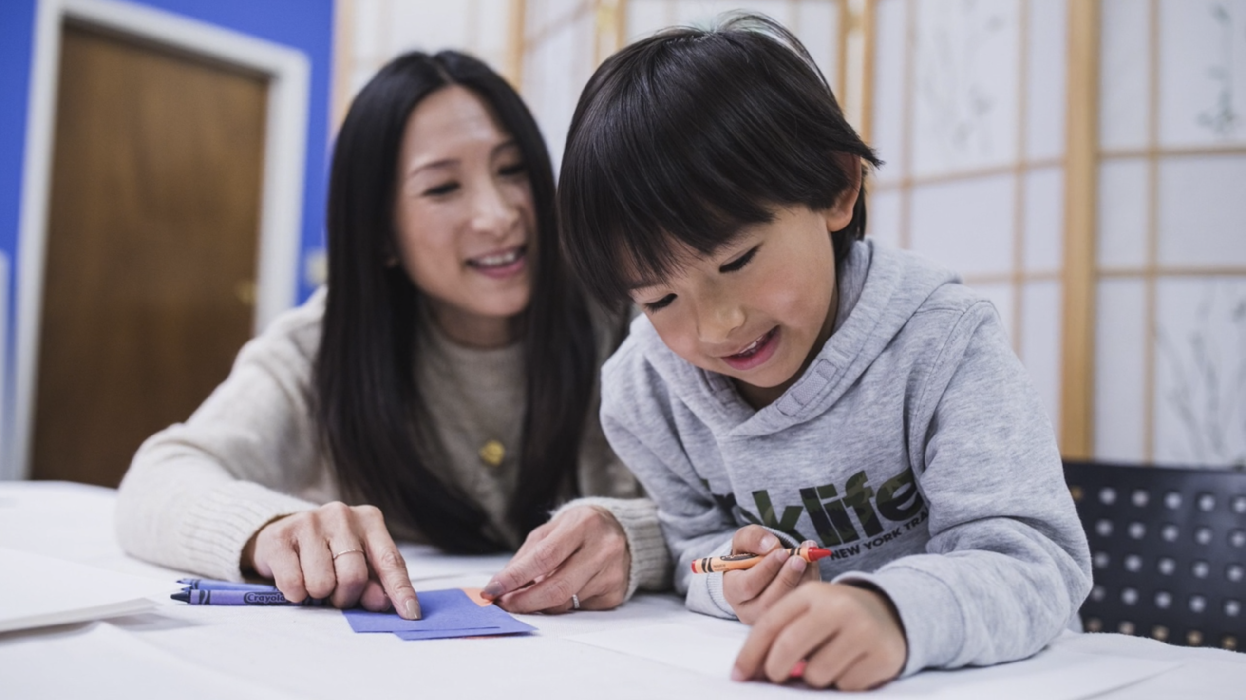 Mother and son enjoy exploring math together at the table.