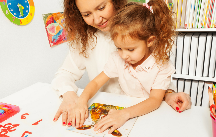 Young girl doing a jigsaw puzzle with her mother