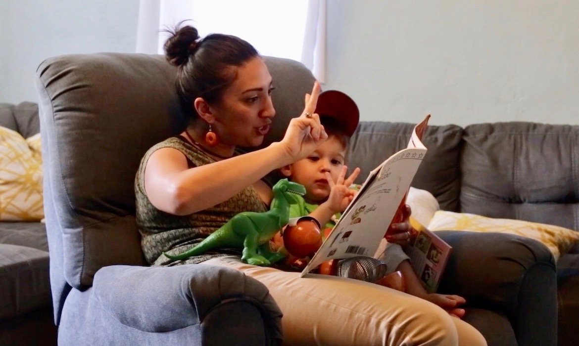 Mom and son read counting books in a chair at home