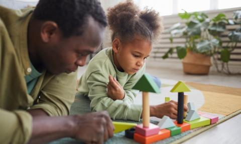 father and daughter play blocks on the floor at home