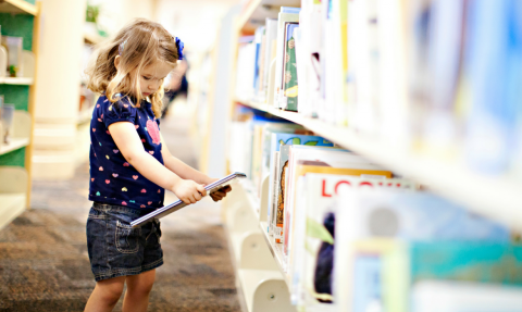 Child choosing a picture book in the library stacks