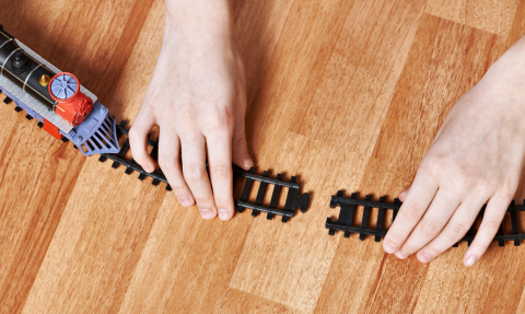 Hands connecting toy railroad tracks