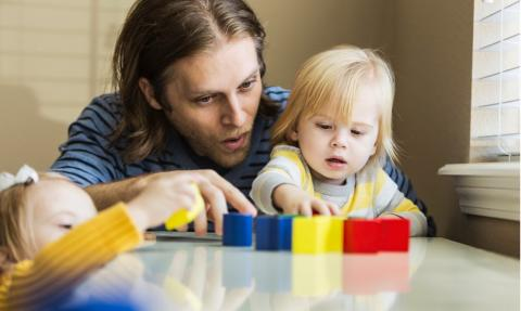 father and children playing with blocks at the table