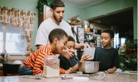 Father prepares meal in kitchen with his sons