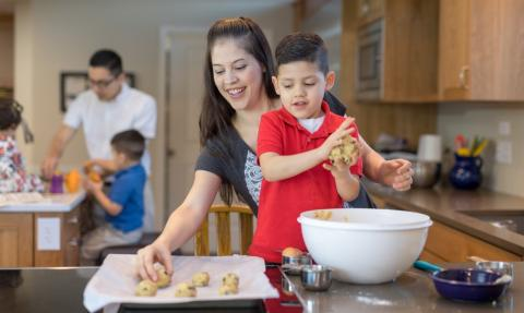 Boy and mother bake cookies in kitchen at home