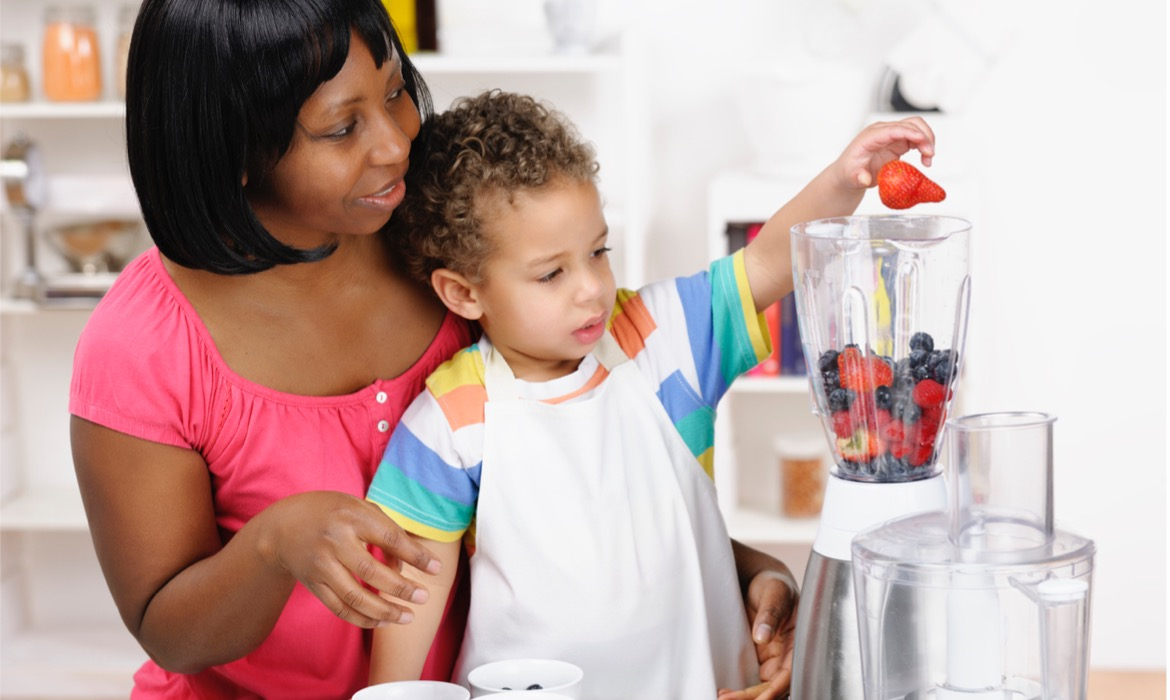 toddler helping his mother preparing a smoothie